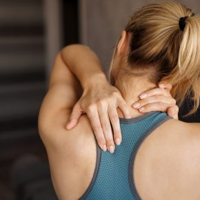 Sports injury concept. Athletic girl feeling pain in her neck against blurred background. Pain after home workout