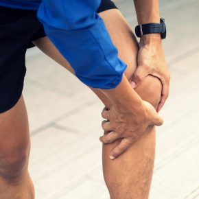 A man wearing a blue Windbreaker jacket., Knee pain after exercise concept.It happens often in athletes practice overtain.In arthritis concept.